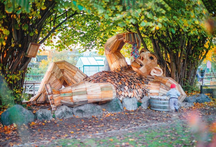 Recycled troll sculpture lying on side by trees from Imagine Exhibitions new exhibit