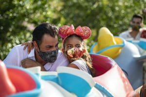 family-on-ride-at-Disneyland-in-masks storytelling after covid