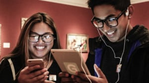 Two young people smile while holding smart devices