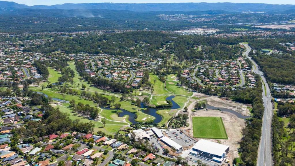 Aerial view of planned community in Gold Coast, Parkwood Village, featuring homes and sporting greens.
