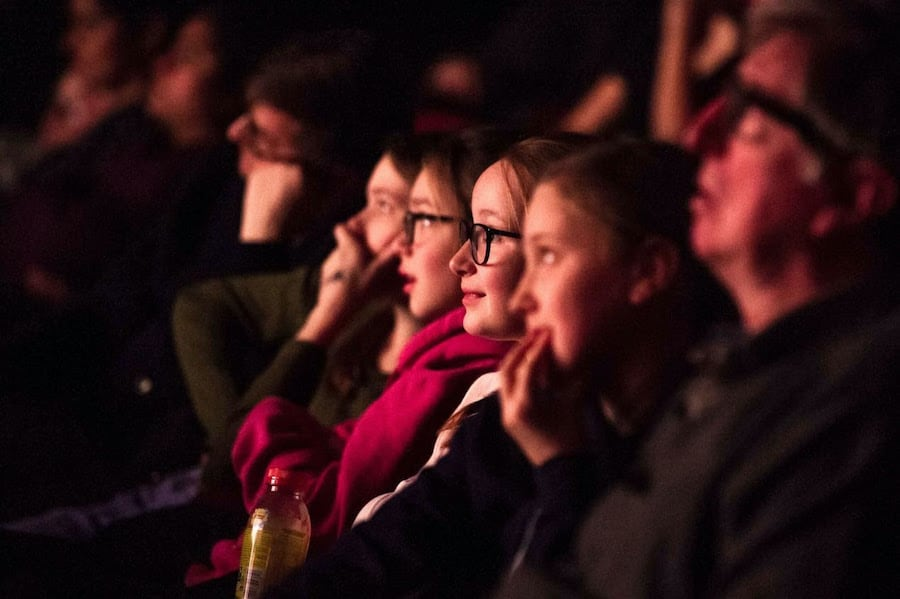 Young people in a theater watching a film