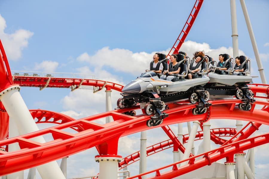 8 young people in jet-shaped roller coaster cars screaming rolling down a red track