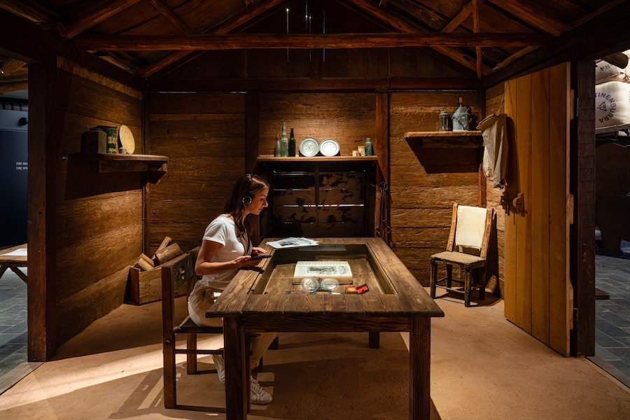 A woman sits at an interactive table inside a cabin exhibit