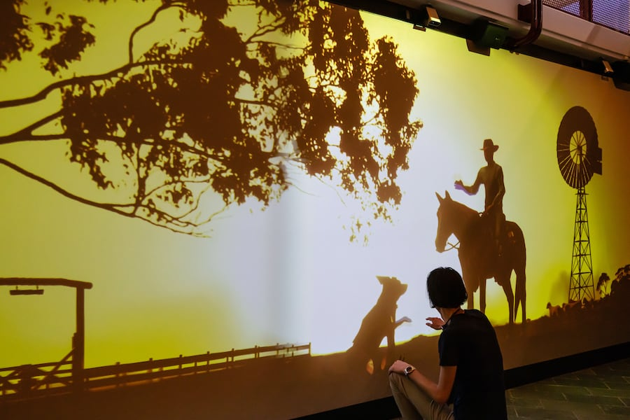 Projection mapped sunset scene of a cattle farmer and a dog