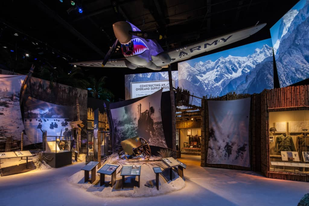 This is an exhibit from the WWII Museum including an overhanging plane and AV screens.