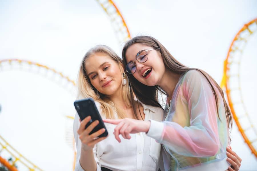 Friends-using-phone-at-theme-park guest engagement