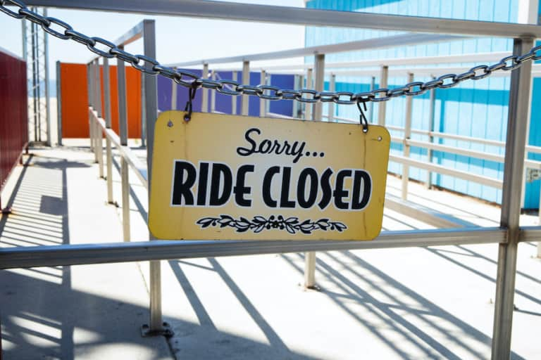 ride closed sign hanging on empty amusement park ride